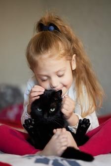 Retrato de uma menina bonita criança que abraça um gato preto com ternura e amor e sorri com felicidade