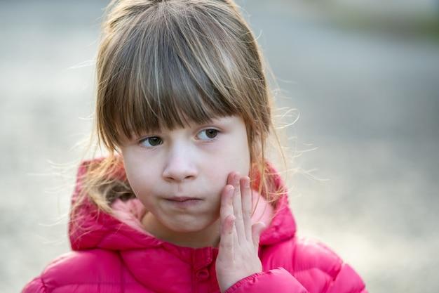 Retrato de uma menina bonita criança segurando a mão para morder a dor ao ar livre.