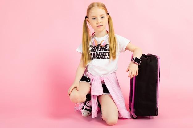 Retrato de uma menina bonita de bermuda, camiseta e tênis altos.