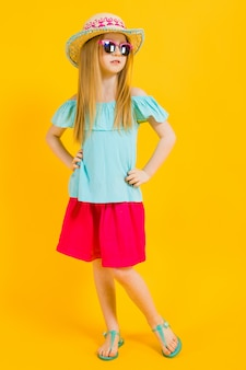 Retrato de uma menina bonita de chapéu, óculos escuros, vestido de verão e sandálias.