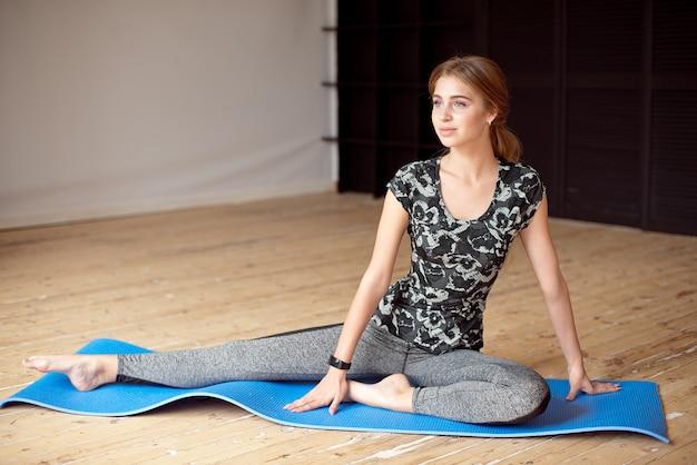 Retrato de uma menina bonita de esportes no sportswear descansando depois de um treino de fitness bebendo água