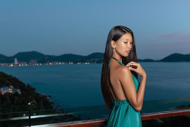 Retrato de uma menina bonita de raça mista em perfil na beira-mar à noite