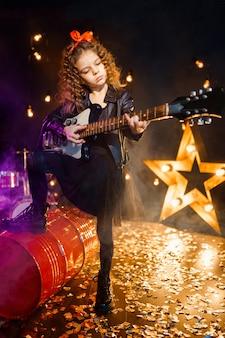 Retrato de uma menina bonita do rock com cabelos cacheados, vestindo jaqueta de couro e tocando guitarra elétrica