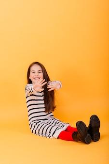 Retrato de uma menina bonita e confiante mostrando emoções e polegares para cima isolados em amarelo Foto Premium