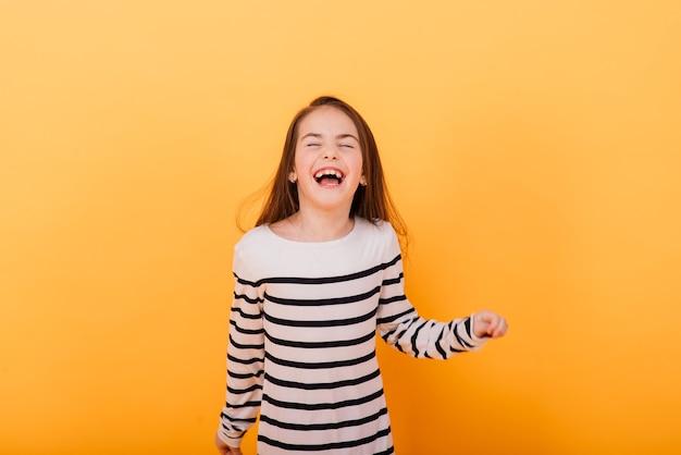 Retrato de uma menina bonita e confiante mostrando emoções e polegares para cima isolados em amarelo
