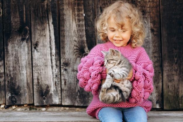 Retrato de uma menina bonita e feliz encaracolada com uma camisola de malha brincando com um gatinho perto de uma parede de madeira