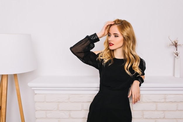 Retrato de uma menina bonita, jovem mulher com cabelos loiros ondulados sensualmente olhando para o lado tocando seu cabelo. usando um vestido preto elegante. parede branca, lareira, lâmpada.