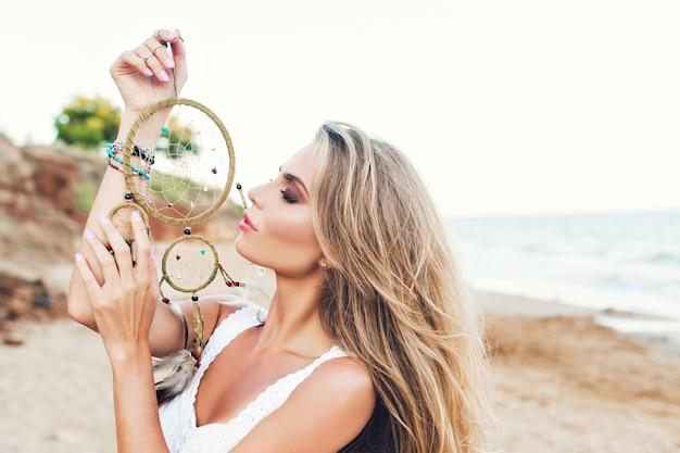 Retrato de uma menina bonita loira com cabelo comprido na praia. segura a ornamentação na mão e mantém os olhos fechados.
