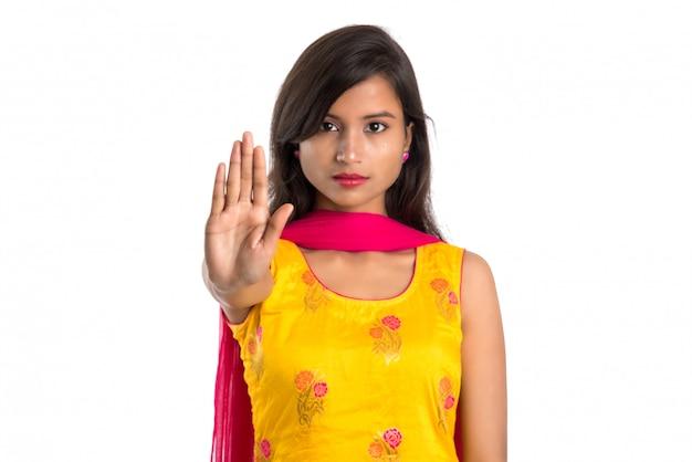 Retrato de uma menina bonita, mostrando o sinal de stop com as palmas das mãos isoladas em um branco