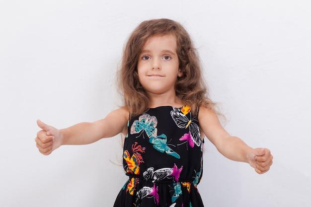 Retrato de uma menina bonita, mostrando os polegares