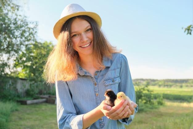 Retrato de uma menina bonita na fazenda com dois filhotes recém-nascidos na mão