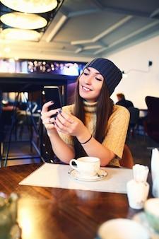 Retrato de uma menina bonita no chapéu usando seu telefone celular no café