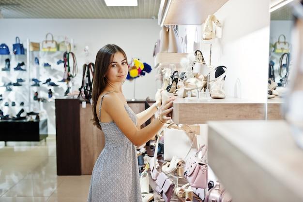 Retrato de uma menina bonita no vestido cinza na loja de sapatos e bolsas.