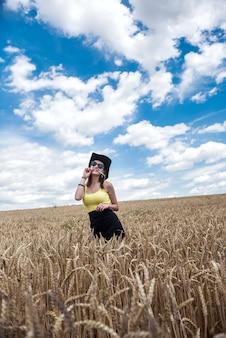 Retrato de uma menina bonita posando no fundo de um campo agrícola, horário de verão