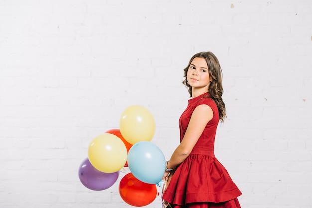 Retrato de uma menina bonita segurando balões coloridos na mão, olhando para longe