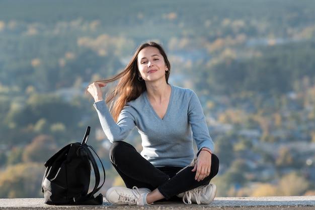 Retrato de uma menina bonita sorridente com uma mochila ao ar livre.