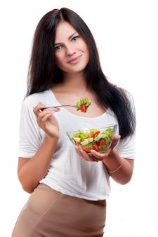 Retrato de uma menina bonita sorrindo e pronto para comer uma tigela de salada de frutas