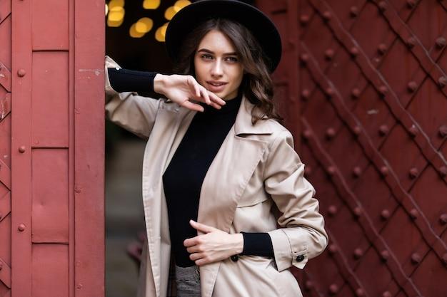 Retrato de uma menina bonita vestida com roupas de outono perto de uma velha porta vintage