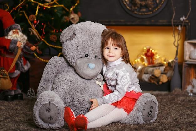 Retrato de uma menina bonitinha abraçando um ursinho de pelúcia cinza macio no interior com decorações de natal