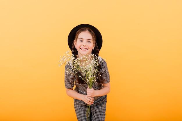 Retrato de uma menina bonitinha com buquê de flores no estúdio em fundo amarelo. parabéns, primavera ou conceito de férias felizes. copie o espaço para o texto