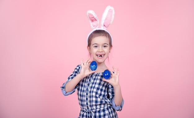 Retrato de uma menina bonitinha com ovos de páscoa em um fundo rosa.