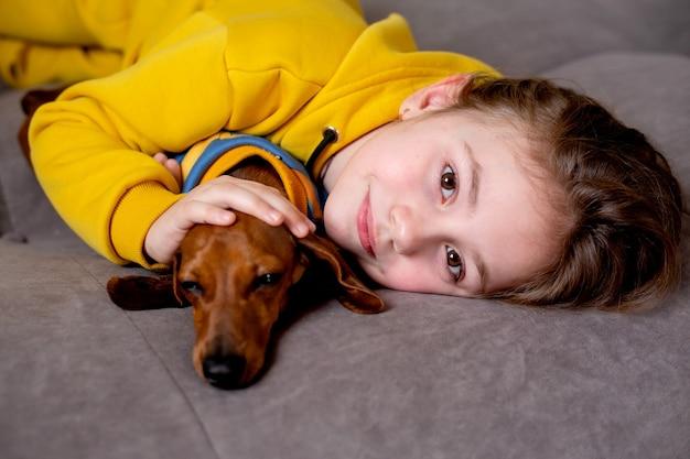 Retrato de uma menina bonitinha com roupas amarelas deitada na cama com um dachshund anão em macacão azul