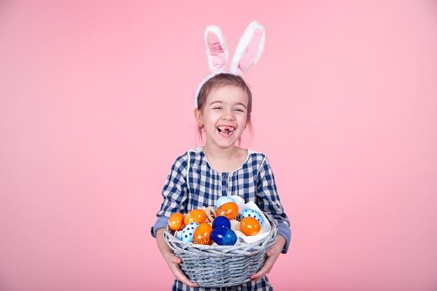 Retrato de uma menina bonitinha com uma cesta de ovo de páscoa em um fundo rosa isolado.