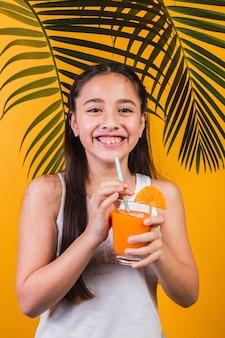 Retrato de uma menina bonitinha desfrutando de suco de laranja em um fundo amarelo.