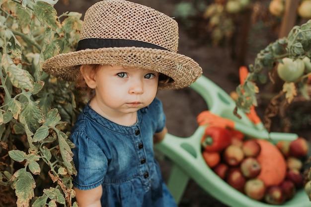 Retrato de uma menina bonitinha em um vestido azul e um chapéu de palha no jardim jovem agricultor