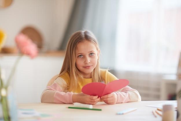 Retrato de uma menina bonitinha segurando um cartão em forma de coração enquanto está sentado à mesa no interior aconchegante de casa, copie o espaço