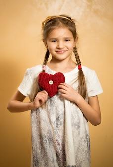 Retrato de uma menina bonitinha segurando um coração vermelho decorativo