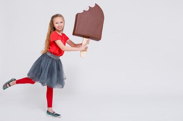 Retrato de uma menina bonitinha segurando um enorme sorvete e copie o espaço sobre o fundo branco
