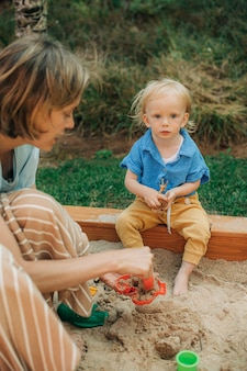 Retrato de uma menina bonitinha sentada na caixa de areia