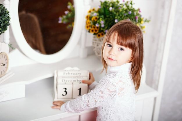 Retrato de uma menina bonitinha sentada perto de um espelho com calendário de madeira nas mãos no interior com decoração chique surrada