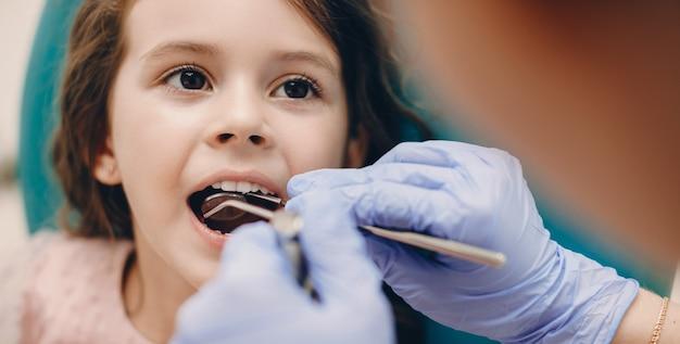 Retrato de uma menina bonitinha, tendo um exame de dentes em estomatologia pediátrica, enquanto olha para o médico.