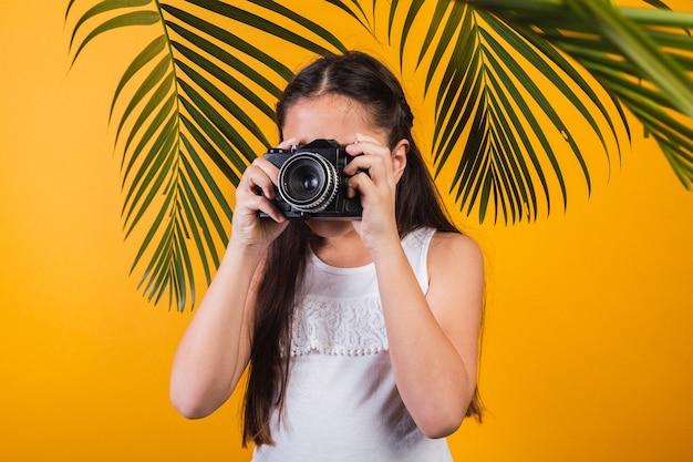 Retrato de uma menina bonitinha tirando fotos com uma câmera em fundo amarelo.