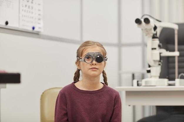 Retrato de uma menina bonitinha usando armação de teste durante o teste de visão na clínica de oftalmologia pediátrica