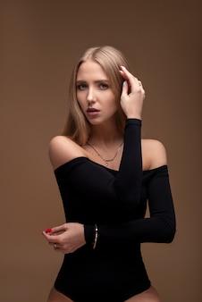 Retrato de uma menina branca branca. jovem modelo com um corpo bonito esporte. loira de biquíni na parede marrom. retrato de uma atraente garota esbelta em lingerie.