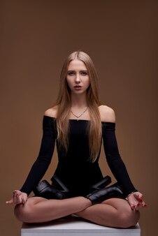 Retrato de uma menina branca branca. jovem modelo com um corpo bonito esporte. loira de biquíni na parede marrom.