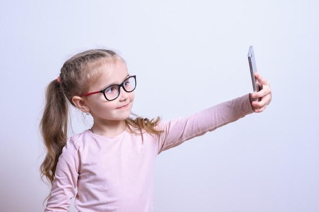 Retrato de uma menina branca fazer selfie em um telefone móvel