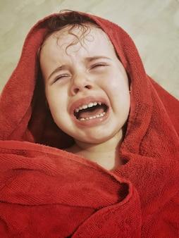 Retrato de uma menina brasileira chorando com uma toalha vermelha na cabeça.