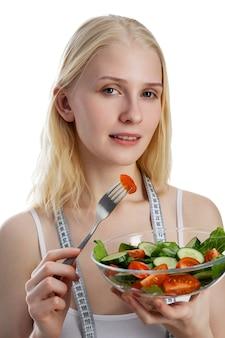 Retrato de uma menina brincalhona feliz comendo salada fresca de uma tigela e piscando isolado sobre uma parede branca.