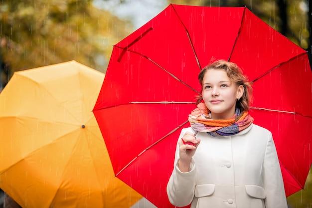 Retrato de uma menina caminhando sob um guarda-chuva vermelho brilhante na cidade de outono