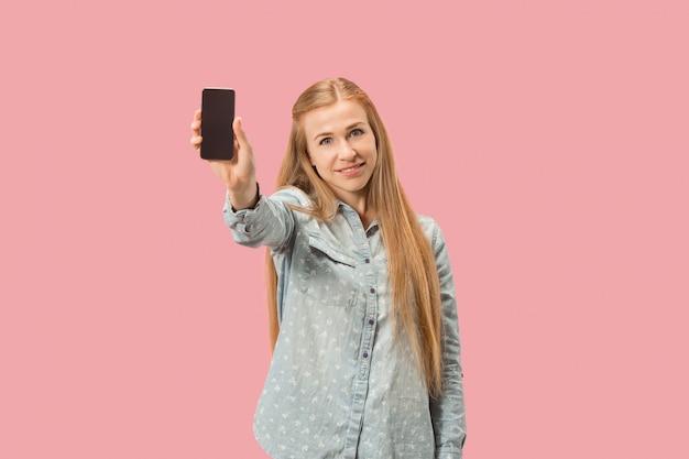 Retrato de uma menina casual confiante, mostrando o telefone móvel de tela em branco, isolado sobre a parede rosa