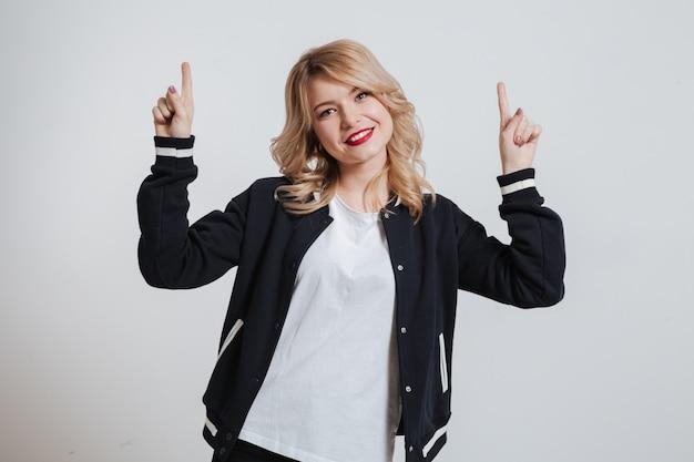 Retrato de uma menina casual feliz apontando dois dedos para cima