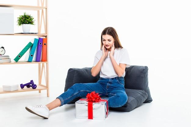 Retrato de uma menina casual, sentado no chão com uma pilha de caixas de presente e olhando para longe isolado sobre a parede branca