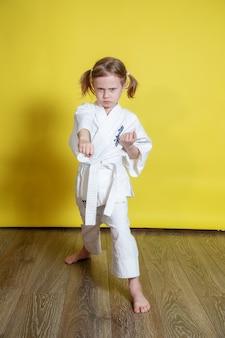Retrato de uma menina caucasiana de 5 anos de quimono praticando karatê contra um fundo amarelo em casa