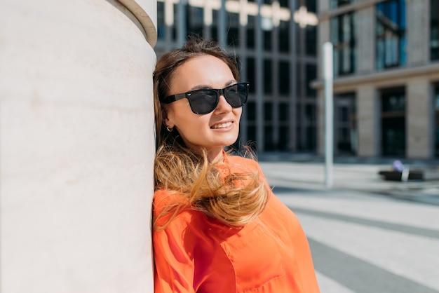 Retrato de uma menina caucasiana de óculos escuros e roupas casuais em uma cidade de verão.