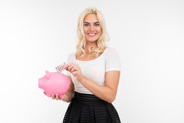 Retrato de uma menina caucasiana em uma saia e camiseta segurando um cofrinho rosa para economizar dinheiro em um fundo de parede branca com espaço de cópia