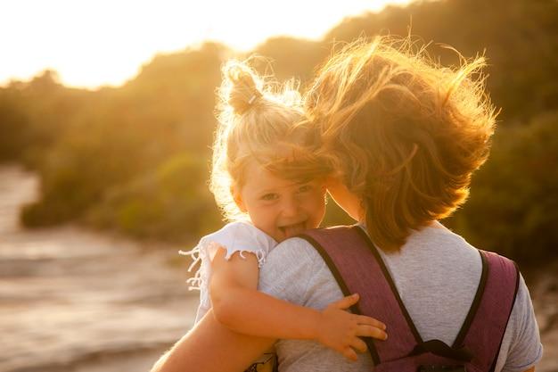 Retrato de uma menina caucasiano de 3 anos com cabelo loiro que mostra sua língua divertidamente.
